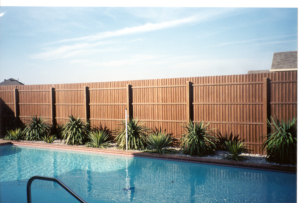 wood-look fiberglass fence around a pool